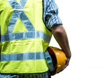Konstruujący mężczyzna pozycję z żółtym zbawczym hełmem odizolowywającym na białym tle fotografia stock