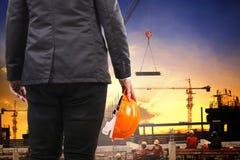 Konstruujący mężczyzna trzyma zbawczego hełm i działanie w budować co Obrazy Royalty Free
