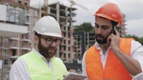 Konstruuje mówi na telefonie komórkowym na budowie i sprawdza pracę pracownik Budowniczy opowiada na smartphone zdjęcie wideo