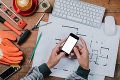 Konstruuje mężczyzna używa mądrze telefon z pustym ekranem zdjęcia stock