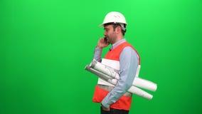 Konstruuje pracownika opowiada z telefonem komórkowym z projektami, zielony parawanowy tło zbiory