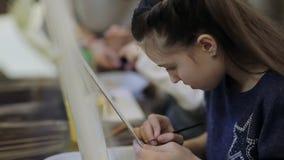 Konstskolan, en grupp av barn med staffli målar en målning med borstar och målarfärger arkivfilmer