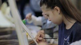 Konstskolan, en grupp av barn med staffli målar en målning med borstar och målarfärger lager videofilmer