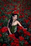Konststående av en flickabrunett på en bakgrund av rosor Royaltyfri Bild