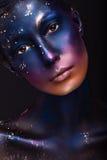 Konststående av en härlig flicka med färgmålarfärg på hennes framsida Fotografering för Bildbyråer