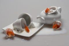 Konststilleben med guldfisken: en vit porslintekanna, två koppar, ett tefat och spillt mjölkar, i skalet av ett fegt ägg, på Royaltyfri Bild