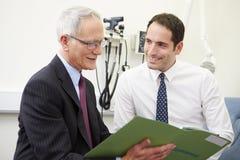 Konsulent Discussing Test Results med patienten fotografering för bildbyråer