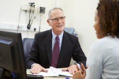 Konsulent Meeting With Patient i regeringsställning royaltyfria foton