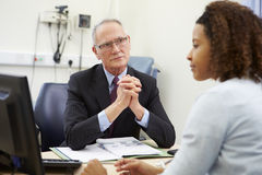 Konsulent Meeting With Patient i regeringsställning royaltyfria bilder