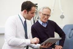KonsulentShowing Patient Test resultat på den Digital minnestavlan royaltyfri bild