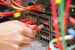 IT konsultant łączy sieć kabel w zmianę w datacenter zdjęcia royalty free