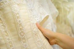 Konsultant pokazuje koronkę na tle ślubne suknie obraz stock