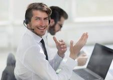 Konsultant siedzi przy jego biurkiem w hełmofonach zdjęcie royalty free