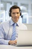 Konsultant w biurze na telefonie z słuchawki, patrzeje przychodził fotografia royalty free