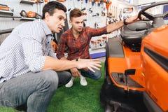 Konsultant w ogrodowych narzędzi sklepie pokazuje klientowi gazonu kosiarza zdjęcia royalty free