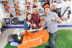 Konsultant w ogrodowych narzędzi sklepie pokazuje klientowi trawa krajacz obraz royalty free