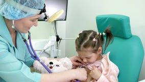 Konsultation av ENT doktorn, förkylning, det medicinska tillvägagångssättet, otolaryngologist behandlar spädbarnet, läkarundersök arkivfilmer