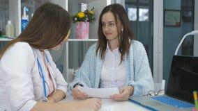 Konsultation med en doktor Kvinnan på mottagande på doktorssamtalen om hans krämpor stock video
