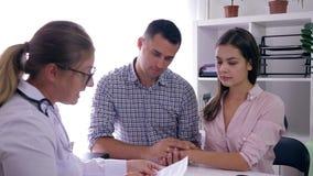 Konsultation om kvinnahälsa, gift par finner ut från doktor om havandeskap i klinikrum stock video