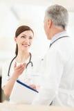 Konsultera med en kollega. Ungt kvinnligt doktorsanseende in för Arkivbild