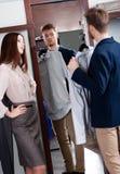 Konsultera med flickvännen, medan välja en skjorta Arkivfoto