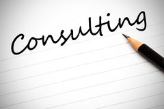 Konsultera som är skriftligt på en notepad royaltyfri fotografi