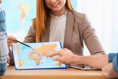 Konsulterande klienter för kvinnlig chef i loppbyrå royaltyfri fotografi
