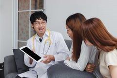 Konsulterande patient f?r ung asiatisk manlig doktor i sjukhuskontor H?lsov?rd- och l?karunders?kningbegrepp royaltyfri foto