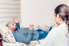 Konsulterande period för psykolog Man att ligga på soffan som klagar om hans problem royaltyfri fotografi