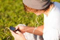 Konsulterande telefon för ung stilig man utomhus royaltyfri fotografi