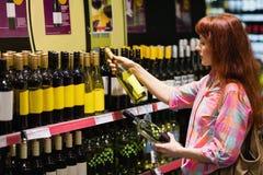 Konsument som tvekar mellan två flaskor av vin Arkivfoto