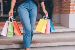 Konsument, zakupy styl życia pojęcie, Szczęśliwa młodej kobiety pozycja i mienie kolorowe torby na zakupy cieszy się wielkiego dz zdjęcie stock