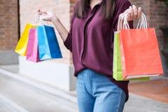 Konsument, zakupy styl życia pojęcie, Szczęśliwa młodej kobiety pozycja i mienie kolorowe torby na zakupy cieszy się wielkiego dz obrazy stock