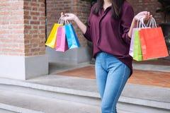 Konsument, zakupy styl życia pojęcie, Szczęśliwa młodej kobiety pozycja i mienie kolorowe torby na zakupy cieszy się wielkiego dz zdjęcia stock