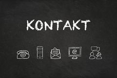`Kontakt` text and icons on a blackboard. Translation: `Contact` stock image