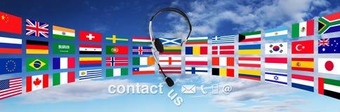 Kontakta begreppet, hörlurar med mikrofon med flaggor på himmel och kontakta oss text Arkivbilder