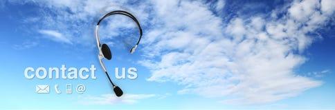 Kontakta begreppet, hörlurar med mikrofon på blå himmel och kontakta oss text Royaltyfria Bilder