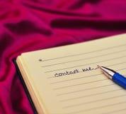 Kontakta mig text på anteckningsboken Royaltyfria Bilder
