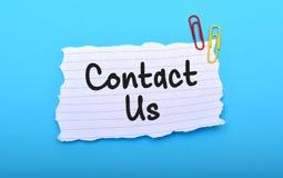 Kontakta oss handen som är skriftlig på papper med blå bakgrund fotografering för bildbyråer