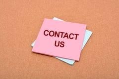 Kontakta oss som är skriftliga på notepaden med bakgrundstextur Royaltyfria Bilder