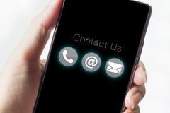 Kontakta oss symboler på smartphonen med handen Royaltyfria Bilder