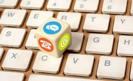 Kontakta oss symboler på tärningbärbar datortangentbordet - kommunikationsbegrepp Arkivbild