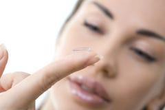 Kontaktlins: Hållande kontaktlins för ung kvinna på fingret i fron Royaltyfri Foto