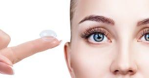 Kontaktlinse auf Zeigefinger nahe schönem weiblichem Gesicht lizenzfreies stockbild