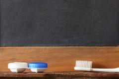 Kontaktlinsebehälter-Kasteneinheit setzte an hölzerne repres Regal der Toilette lizenzfreie stockfotografie