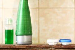 Kontaktlinsebehälter-Kasteneinheit setzte an hölzerne repres Regal der Toilette lizenzfreies stockfoto