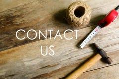 Kontaktuje się my pisać na drewnianym tle Ciesielki pojęcie z arkany, młoteczkowej i pomiarowej taśmą, zdjęcia royalty free