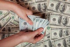 kontant hand Vinst besparingar Bunt av dollar en person som räknar pengar mot bakgrunden av pengar, framgång, motivati Fotografering för Bildbyråer
