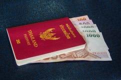Kontant och thailändskt rött räkningspass Royaltyfri Bild