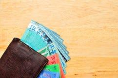 Kontant plånbok för pengar på trätabellen Arkivbild